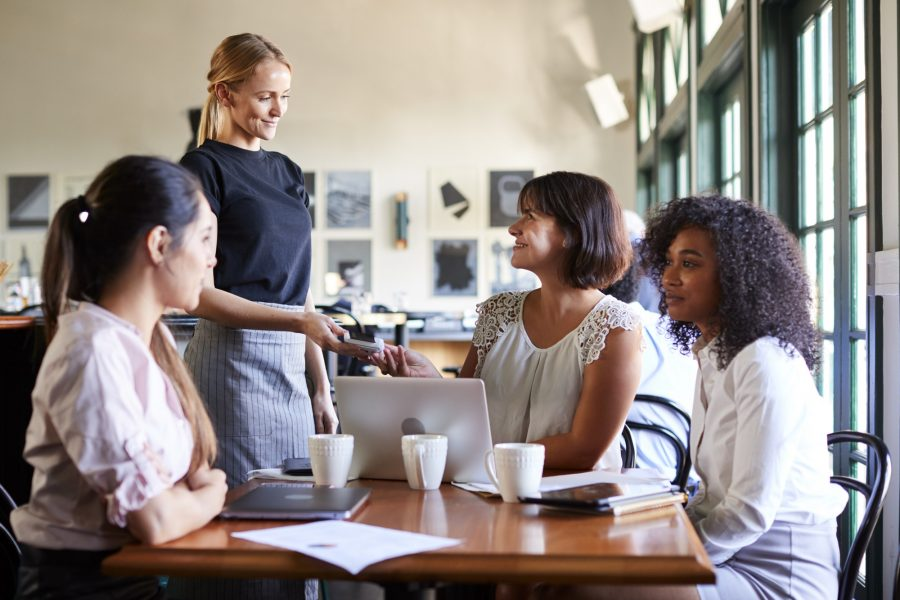 Businesswomen Paying Bill At Meeting Around Table In Coffee Shop